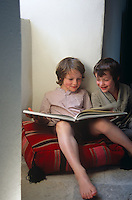 Two boys share a large cushion and giggle over a book