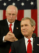 United States Vice President Richard Cheney applauds U.S. President George W. Bush as he makes a point while delivering the State of the Union address from the House Chamber in the U.S. Capitol on January 20, 2004.  Bush delivered his remarks to a Joint Session of Congress.  <br /> Credit: Kevin Lamarque / Pool via CNP