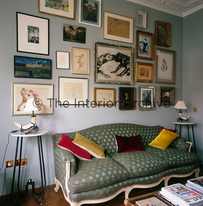 A collection of various artworks is informally displayed in a group on the wall in this corner of the living room