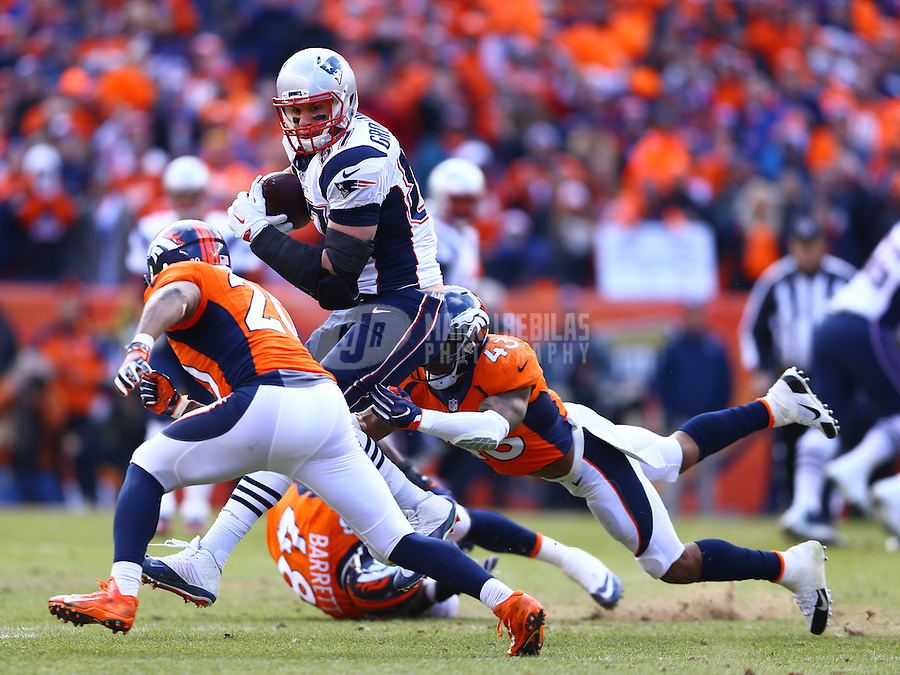 Jan 24, 2016; Denver, CO, USA; New England Patriots tight end Rob Gronkowski (87) is tackled by diving Denver Broncos safety T.J. Ward (23) in the AFC Championship football game at Sports Authority Field at Mile High. Mandatory Credit: Mark J. Rebilas-USA TODAY Sports