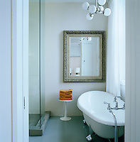 A large framed mirror hangs against a mosaic-tiled wall in this bathroom which is furnished with a modern ball-and-claw bath