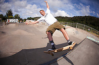 A caucasian male skateboarder grinds the coping at the Banzai Skate Park on the North Shore of O'ahu
