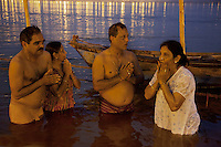 India. Uttar Pradesh state. Allahabad. Maha Kumbh Mela. Two couples of Indian Hindu devotees take a holy dip and prays in Sangam at night. The Kumbh Mela, believed to be the largest religious gathering is held every 12 years on the banks of the 'Sangam'- the confluence of the holy rivers Ganga, Yamuna and the mythical Saraswati. In 2013, it is estimated that nearly 80 million devotees took a bath in the water of the holy river Ganges. The belief is that bathing and taking a holy dip will wash and free one from all the past sins, get salvation and paves the way for Moksha (meaning liberation from the cycle of Life, Death and Rebirth). Bathing in the holy waters of Ganga is believed to be most auspicious at the time of Kumbh Mela, because the water is charged with positive healing effects and enhanced with electromagnetic radiations of the Sun, Moon and Jupiter. The Maha (great) Kumbh Mela, which comes after 12 Purna Kumbh Mela, or 144 years, is always held at Allahabad. Uttar Pradesh (abbreviated U.P.) is a state located in northern India. 6.02.13 © 2013 Didier Ruef