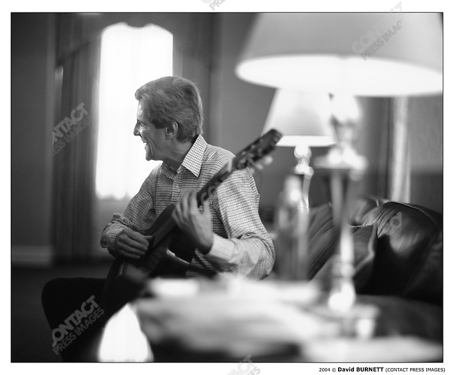 John KERRY, Democratic candidate for president, plays guitar in his hotel room before the start of the Iowa caucuses. Des Moines, Iowa, January 19, 2004