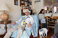 "Carlos Arredondo, 57, (left) and his wife Melida Arredondo, 52, are seen in their home in Roslindale, Boston, Massachusetts, USA, on Sat., March 31, 2018. Arredondo is well known as the ""man in the cowboy hat"" who helped out in the aftermath of the Boston Marathon Bombing in 2013. Carlos is wearing a jacket that he has used to create a t-shirt design for when he runs the Boston Marathon later this year. Though he has run the race unofficially previously, this will be the first time he runs it ""legally,"" he says. Their dog, Buddy, age 18, can be seen on the floor. Carlos says he often accidentally calls Buddy by his son's name, Brian. Brian Arredondo died by suicide in 2011 after a battle with depression following the 2004 death of Arrendondo's other son  Marine Lance Corporal Alexander Scott Arredondo, who was killed while serving in Iraq."