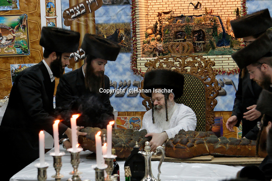 Israel, Bnei Brak. Succot holiday at the Premishlan congregation. A Tish with the Rebbe (a gathering of the Hasidim with their Rebbe). The Rebbe is cutting the Challah bread<br />