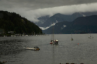Yacht in Deep Cove Bay with clouds above the mountains over Mount Seymour provincial park. Deep Cove, Burrard Inlet, Vancouver, British Columbia, Canada.