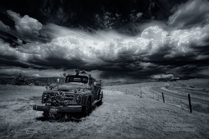 Stormy Day for Engine 3 (Infrared).  This antique fire truck is on display outside the Four Mile fire station south of Cripple Creek, Colorado.  In addition to withstanding summer monsoon storms like the one threatening it in this photo (and severe winter weather as well), it also has been asked to serve as a vehicle for Christmas lights, which are left in place all year (along with the cord to power them, visible above the front bumper).  It endures all of this with the quiet strength, grace, and pride with which it conducted itself while on active duty many years ago.<br /> <br /> Image © 2019 James D Peterson