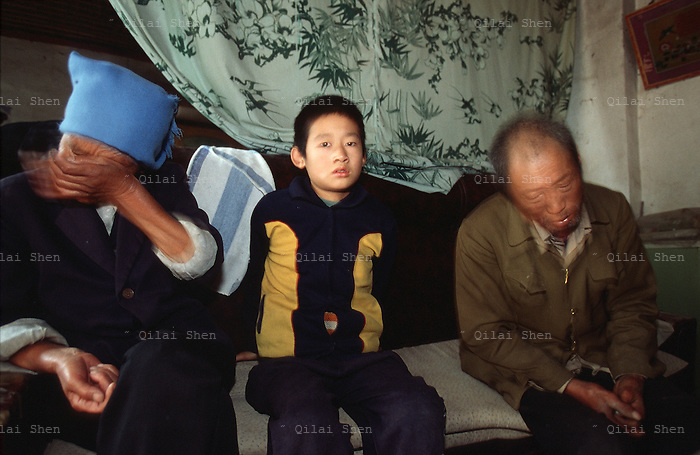 QSFeature02AIDS020 20020212 DONGGUAN, CHINA:  Orphan Jian Guo with his grieving grandparents at their home in Dongguan Village, Henan Province, China 12 February 2002. Both of Jian Guo's parents died from AIDS. Over 700,000 peasant farmers have contracted the HIV virus when they participated in the unregulated blood selling/buying boom of the early and mid nineties. Ding died shortly after this photo was taken..Photo by: Qilai Shen...