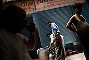 A milk man is seen pouring milk while customers  have their tea next to a tea stall in Kinari bazaar of Chandni Chowk, in the old city of Shahjanabad, popularly known as Old Delhi.