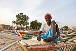 A man sits on one of the colorfully painted fishing boats that line the beach at this fish market in Dakar, Senegal.