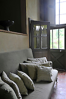 An antique banquette in the living room has been covered in a contemporary grey linen with matching scatter cushions