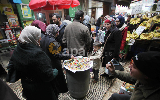 """Palestinians eat candy during a ritual ceremony to commemorate the birth of the Prophet Mohammed, known in Arabic as """"al-Mawlid al-Nabawi"""", in the West Bank city of Nablus on December 11, 2016. Photo by Nedal Eshtayah"""