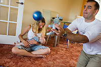 A woman sitting crossed-legged at home on her living room carpet,   breastfeeding her baby whilst her husband plays a ball game with their other child.<br /> <br /> 09/07/2011<br /> Hampshire, England, UK