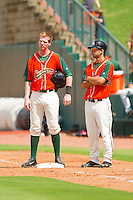 Colin Moran (14) of the Greensboro Grasshoppers hangs out with first base coach Anthony Gomez (2) during a pitching change in the South Atlantic League game against the Augusta GreenJackets at NewBridge Bank Park on August 11, 2013 in Greensboro, North Carolina.  The GreenJackets defeated the Grasshoppers 6-5 in game one of a double-header.  (Brian Westerholt/Four Seam Images)