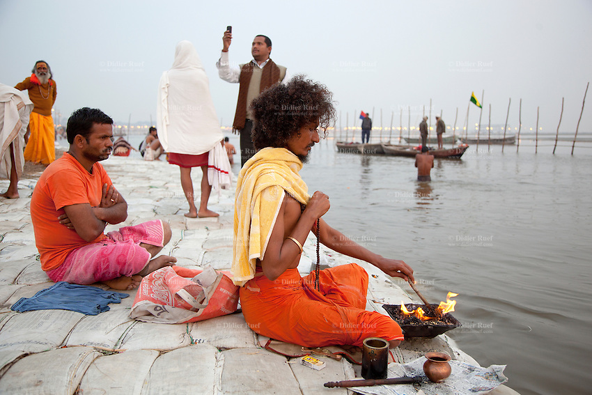 India. Uttar Pradesh state. Allahabad. Maha Kumbh Mela. During a puja in Sangam, an ascetic man makes a fire and worships the river Ganges, considered as a deity. An Hindu devotee takes pictures with his mobile phone. Puja (reverence, honour, adoration, or worship) is a religious ritual performed by Hindus as an offering to various deities. The Kumbh Mela, believed to be the largest religious gathering is held every 12 years on the banks of the 'Sangam'- the confluence of the holy rivers Ganga, Yamuna and the mythical Saraswati. In 2013, it is estimated that nearly 80 million devotees took a bath in the water of the holy river Ganges. The belief is that bathing and taking a holy dip will wash and free one from all the past sins, get salvation and paves the way for Moksha (meaning liberation from the cycle of Life, Death and Rebirth). Bathing in the holy waters of Ganga is believed to be most auspicious at the time of Kumbh Mela, because the water is charged with positive healing effects and enhanced with electromagnetic radiations of the Sun, Moon and Jupiter. The Maha (great) Kumbh Mela, which comes after 12 Purna Kumbh Mela, or 144 years, is always held at Allahabad. Uttar Pradesh (abbreviated U.P.) is a state located in northern India. 6.02.13 © 2013 Didier Ruef