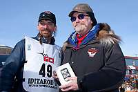 Lance Mackey is congratulated by Gary Samuelson of GCI after winning his 4th consecutive Iditarod in Nome, Alaska