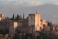 The alcazaba or defensive fortress of the Alhambra Palace, Granada, Andalusia, Southern Spain, with visitors on the roof. The Alhambra was begun in the 11th century as a castle, and in the 13th and 14th centuries served as the royal palace of the Nasrid sultans. The huge complex contains the Alcazaba, Nasrid palaces, gardens and Generalife. Behind are the snow-capped peaks of the Sierra Nevada. Granada was listed as a UNESCO World Heritage Site in 1984. Picture by Manuel Cohen