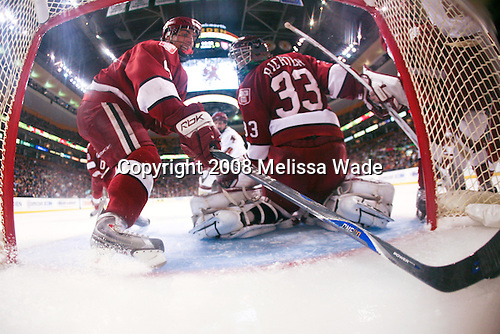 Jimmy Fraser (Harvard 9) retrieves the puck behind Kyle Richter (Harvard 33) as Matt Greene (BC 14) heads in. The Boston College Eagles defeated the Harvard University Crimson 6-5 in overtime on Monday, February 11, 2008, to win the 2008 Beanpot at the TD Banknorth Garden in Boston, Massachusetts.