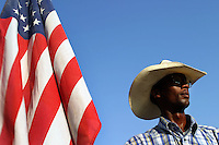 A cowboy at a small African-American rodeo outside of Houston holds the American flag in 2004.