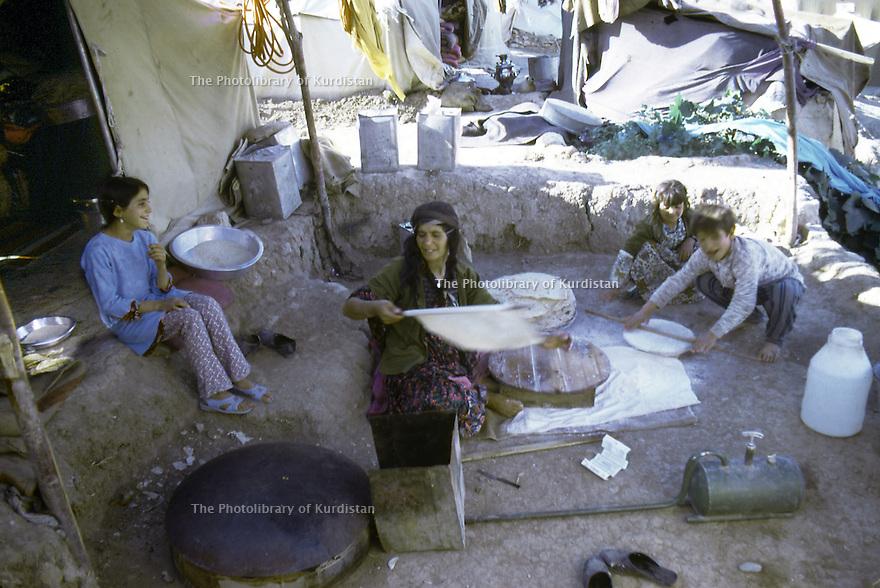 Iran 1974.Camp de réfugiés kurdes à Nelliwan, préparation du pain sous une tente.Iran 1974.Kurdish refugees' camp, woman  cooking bred for her family under a tent
