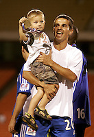 Igor Simutenkov celebrates with his son after Kansas City's 1-0, over Chicago to win the US Open Cup, at Arrowhead Stadium, in Kansas City, MO, Wednesday, Sept., 22, 2004.