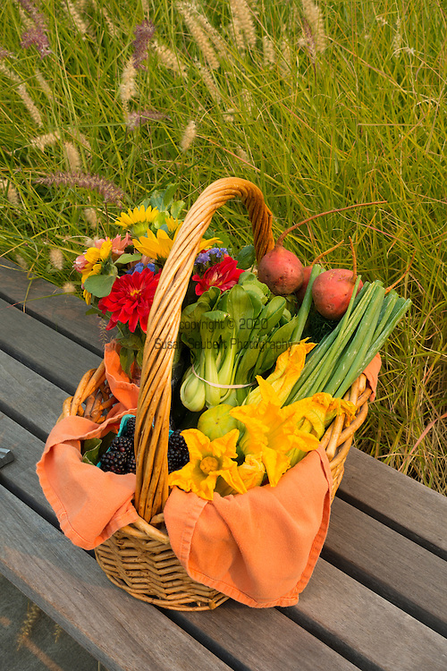a basket of fresh vegetables and flowers on a wood bench near grass