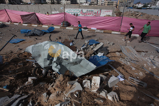 """Palestinians inspect the rubble of a training camp used by Hamas after it was hit by an Israeli missile strike in Gaza City, early Thursday, June 19, 2014. The Israeli military said five rockets were fired from Hamas-controlled Gaza into Israel. One rocket struck a house in southern Israel, causing damage but no injuries. Early Thursday, Israel responded with a series of airstrikes on """"terror activity"""" sites in Gaza. It said """"direct hits"""" were confirmed. There were no immediate reports of injuries. Photo by Ashraf Amra"""