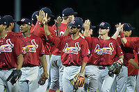 Eliezer Alvarez (center) high fives teammates after their victory over the Burlington Royals at Burlington Athletic Park on August 22, 2015 in Burlington, North Carolina.  The Cardinals defeated the Royals 9-3. (Brian Westerholt/Four Seam Images)