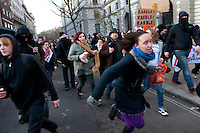 Students run through the streets to avoid being 'kettled' by police during a student demonstration in Westminster, central London on the day the government passed a bill to increase university tuition fees.