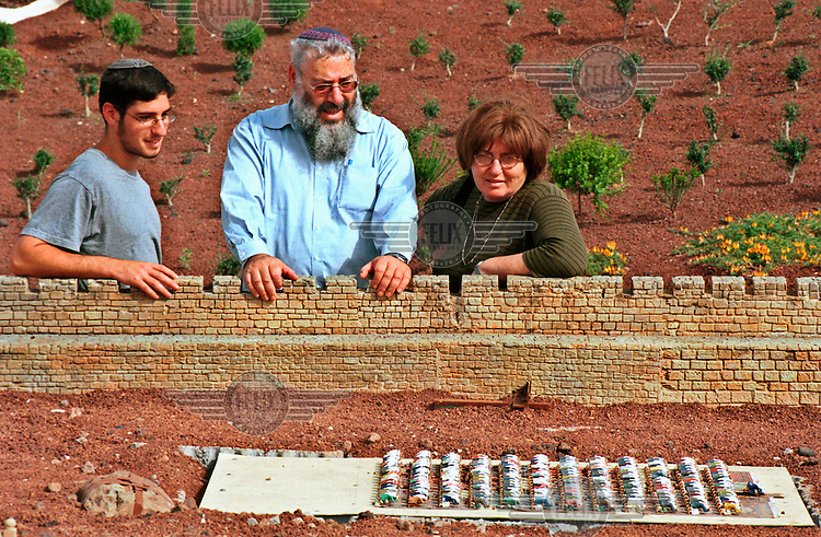 Jewish Israelis look at a model of Muslim worshippers in the Temple Mount, in the Mini Israel tourist attaction.