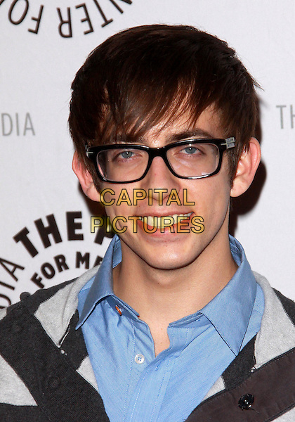 "KEVIN McHALE.27th Annual Paley Fest  presents  ""Glee""  held at the Saban Theatre, Beverly Hills, California, USA..March 13th, 2010.headshot portrait black blue grey gray striped glasses smiling .CAP/ADM/TC.©T. Conrad/AdMedia/Capital Pictures."