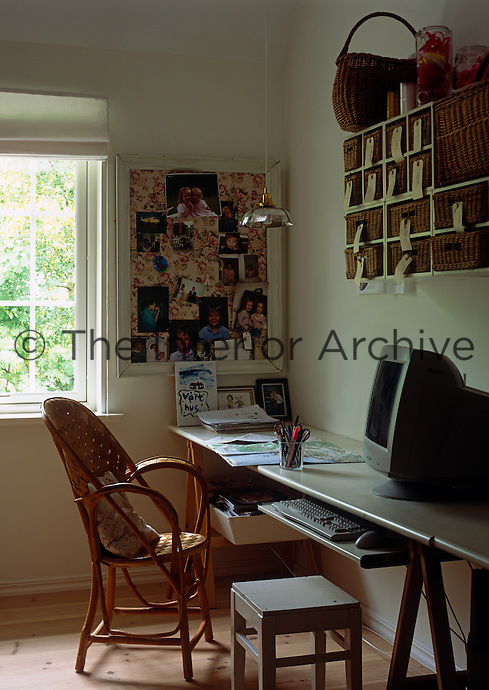 A small study/home office with a wall-mounted storage unit of wicker baskets