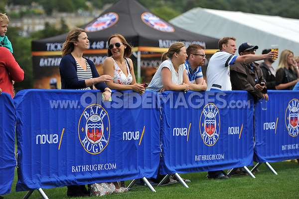 Bath supporters share a joke whilst watching the action from the sidelines. Pre-season friendly match, between Bath Rugby and the Scarlets on August 16, 2014 at the Recreation Ground in Bath, England. Photo by: Patrick Khachfe / Onside Images
