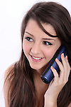 A young woman talking on a cordless phone