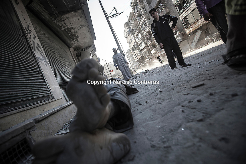 A dead body of a Syrian civilian lies down on the street outside a hospital as it awaits for its relatives to pick it up. The body was arrived dead from Hananu district during the heavy mortar shelling in Aleppo City.