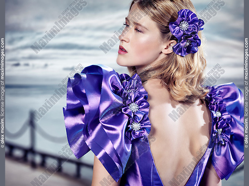 Beauty portrait of a young blond woman wearing a blue evening dress with open back at waterfront outdoors