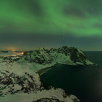 Northern lights shine in sky over Kvalvika beach from summit of Ryten, Moskenesøy, Lofoten Islands, Norway