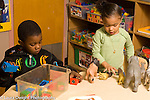 Day Care Center 2-3 year olds boy and girl playing separately side by side girl talkin t herself as she plays with plastic animals, boy playing with magnet blocks