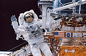 Astronaut Steven L. Smith waves at in-cabin crewmates while working near the foot restraint of the remote manipulator system (RMS) during the third day of extravehicular activity (EVA-3) to service the Hubble <br /> Space Telescope (HST). Astronaut Mark C. Lee, payload commander who shared space walk chores with Smith, is out of frame.<br /> Credit: NASA via CNP