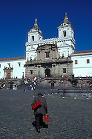 Man carrying a red shoeshine box crossing the Plaza San Francisco in the Old Town, Quito, Ecuador. The Monastery of San Francisco is in the Background. Old Quito was made a UNESCO World Heritage Site in 1978.