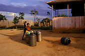 Acre State, Amazon, Brazil. Two boys with milk churns in an Amazon farm.