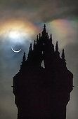 Picture shows today's solar eclipse as seen above the Wallace Monument in Central Scotland at 9.33am - the UK and northern Europe have glimpsed the best solar eclipse since 1999 when the area was plunged into darkness as the Moon came between the Earth and the Sun. The deep shadow formed first in the North Atlantic and then swept up into the Arctic, ending at the North Pole. In all parts of the UK the eclipse reached at least 83% and the darkness peaked at about 09:35 GMT. Clear viewing opportunities were restricted by the cloud cover that shrouded much of the country, which will not see a solar eclipse on this scale again until 2026. The National Wallace Monument - known as the Wallace Monument - stands on the summit of Abbey Craig, a hilltop at near Stirling in Scotland. It commemorates Sir William Wallace, a 13th-century Scottish hero. Completed in 1869 to the designs of architect John Thomas Rochead, the monument is a 67-metre (220 ft) sandstone tower, built in the Victorian Gothic style on a spot where from where Wallace was said to have watched the gathering of the army of King Edward I of England, just before the Battle of Stirling Bridge - picture by Donald MacLeod 20.3.15 clanmacleod@btinternet.com www.donald-macleod.com all rights reserved - 07702 319 738