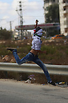 A Palestinian hurls stones towards Israeli policemen during clashes following a demonstration against the Israeli police raid on Jerusalem's al-Aqsa mosque in the West Bank, Jewish settlement of Beit El, north of Ramallah September 29, 2015. New clashes broke out between Palestinians and Israeli police who stormed Jerusalem's flashpoint Al-Aqsa mosque compound, as an expected increase in Jewish visitors to the site over the Sukkot holiday boosted tensions. Jews are allowed to visit the site, but cannot pray to avoid provoking tensions. Muslims fear Israel will seek to change rules governing the compound, which is located in Israeli-annexed east Jerusalem. Photo by Shadi Hatem