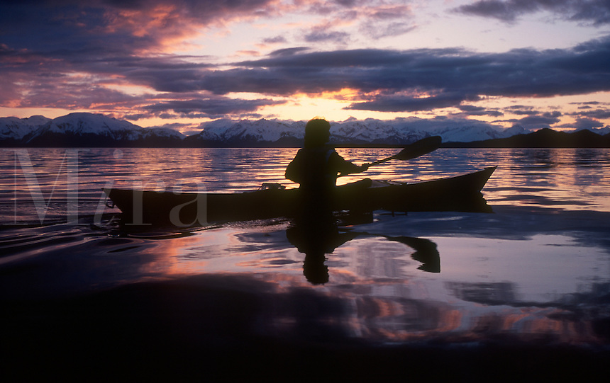 A kayaker paddles into Berners Bay at sunset with the Chilkat Mountain Range in the background.