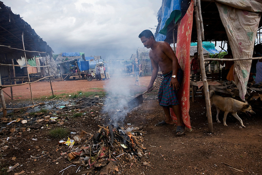 Va Savoeun, a former Dey Krahorm resident and chief of Pthas Khiev community, sweeps rubbish into a fire near a makeshift home at the relocation site provided for Dey Krahorm evictees in Phnom Bat commune, in Kandal province's Ponhea Leu district, September 9, 2010. Police and construction workers employed by local developer 7NG Group forcibly evicted Dey Krahorm's remaining 144 families and leveled their homes on January 24, 2009. The families were given 4-metre x 6-metre plots of land, on which they have build makeshift shelters of wood, mud, tarpaulin and corrugated tin. Va Savoeun said that 467 former Dey Krahorm families and vendors had been relocated to Pthas Khiev community, though only 222 families are currently residing there. The rest have returned to Phnom Penh to seek employment because there are few job opportunities at the relocation site. Following the eviction, the families were sent to live in temporary shelters in Damnak Trayeung village in Dangkor district. They were relocated yet again to Kandal province's Ponhea Leu district on December 12 of last year. He says that residents have no way of earning a living because the relocation site os over 40 kilometeres from Phnom Penh.