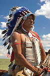 An Indian Chief dressed in full regalia, and on horseback, pauses for a moment against a vibrant Montana blue sky for picture taking after performing the reenactment of the annual Battle of the Little Bighorn in Hardin Montana. Model Release.