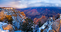 Day dawns on another incoming snowstorm over the mostly shadowed and already snow-covered Grand Canyon, seen briefly from the South Rim in January 2008. Arizona. Grand Canyon National Park.