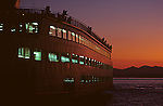 Ferry boat with passengers looking out over Puget Sound and Olympic Mountains at sunset Seattle Washington State USA