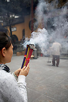 A woman prays while burning an incense offering at the Jade Buddha Temple.<br /> <br /> To license this image, please contact the National Geographic Creative Collection:<br /> <br /> Image ID: 2169198  <br /> <br /> Email: natgeocreative@ngs.org<br /> <br /> Telephone: 202 857 7537 / Toll Free 800 434 2244<br /> <br /> National Geographic Creative<br /> 1145 17th St NW, Washington DC 20036
